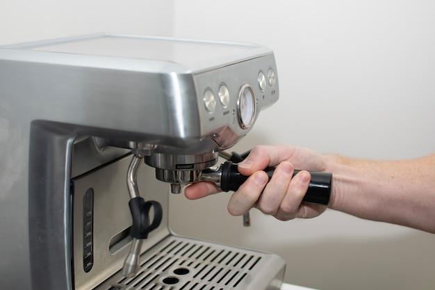 De hand van barista plaatst de koffielepel in het koffiezetapparaat
