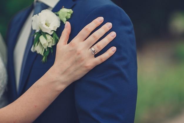 De hand van bruid omhelst haar bruidegom