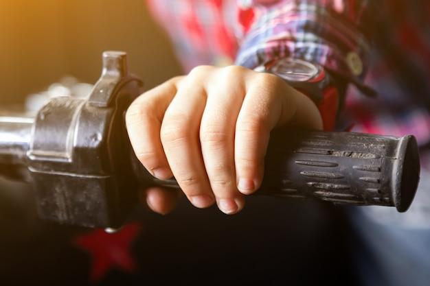 De hand van close-upkinderen op het handvat van een oude motorfiets