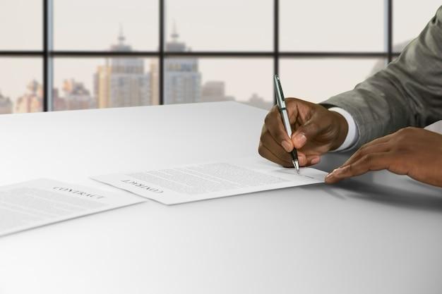 De hand van de afro-zakenman tekent contract. man ondertekening contract in de stad. hij ging akkoord met het voorstel. goed salaris en mooi vooruitzicht.