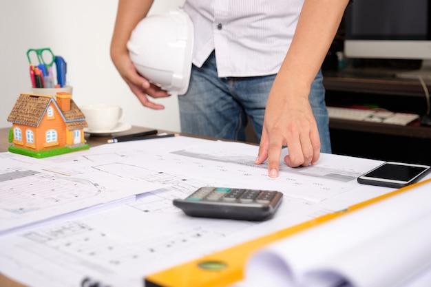 De hand van de architect die naar de blauwdruk richt om het werk aan aannemer te presenteren.