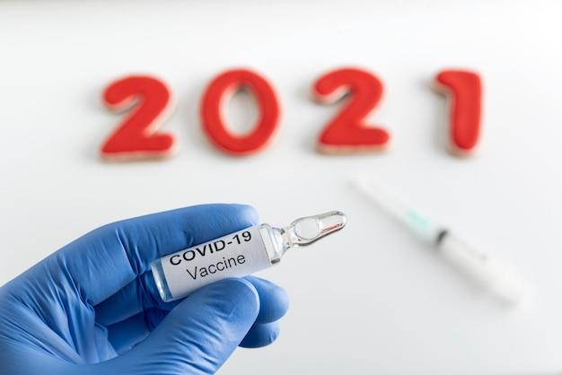 De hand van de arts houdt een ampul met het covid-19-vaccin vast tegen inscriptie 2021-achtergrond.