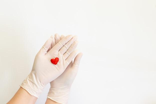 De hand van de arts in de handschoen houdt het hart vast.