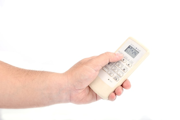 De hand van de aziatische man houdt een afstandsbediening van de airconditioner vast voor het openen, sluiten of aanpassen van de temperatuur geïsoleerd op een witte achtergrond.