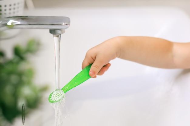 De hand van de baby houdt een tandenborstel onder een stroom van waterclose-up thuis in het badkamersconcept c...