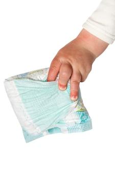 De hand van de baby houdt vuile die luiers op het wit worden geïsoleerd