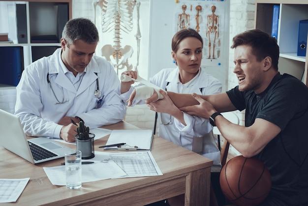 De hand van de basketbalspeler doet pijn in het ziekenhuis