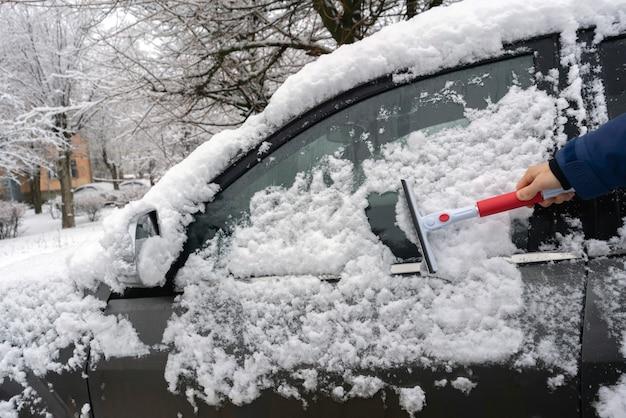 De hand van de bestuurder die de auto 's morgens voor de reis uit de sneeuw haalt