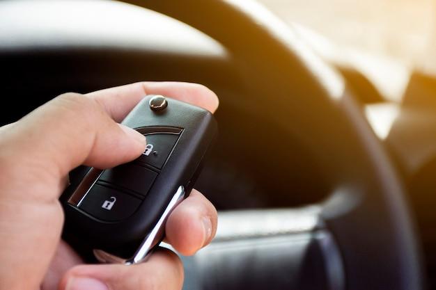 De hand van de bestuurder wordt op de sleutelloze afstandsbediening van de auto gedrukt.