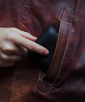 De hand van de blanke haalt een portemonnee uit de zak van iemand anders.