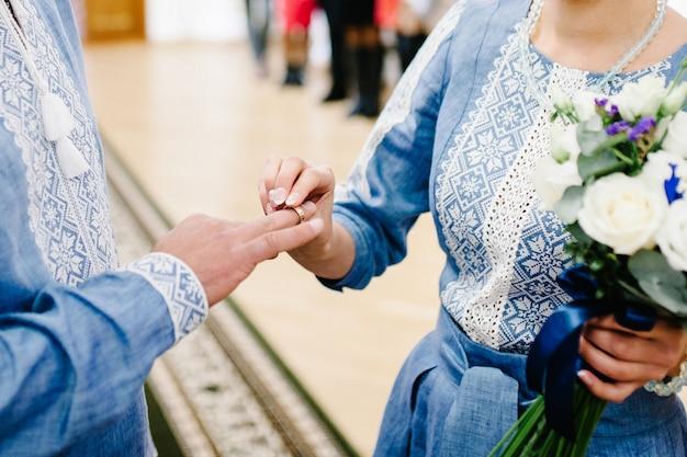 De hand van de bruid draagt een gouden verlovingsring om de vinger van de bruidegom. trouwdag.