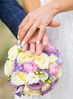 De hand van de bruid met een trouwring ligt op de hand van de bruidegom op de achtergrond van het bruidsboeket. handen van de pasgetrouwden op de achtergrond van het boeket van de bruid