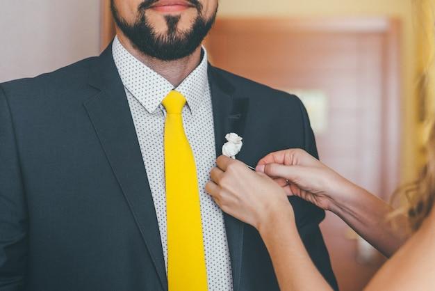 De hand van de bruid zet een corsagesbloem op