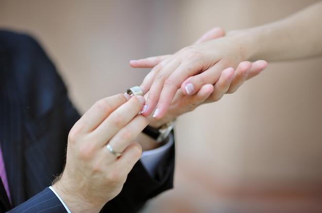 De hand van de bruidegom die een trouwring op de vinger van de bruid zet