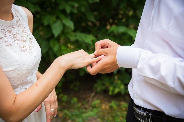 De hand van de bruidegom zetten een trouwring om de vinger van de bruid