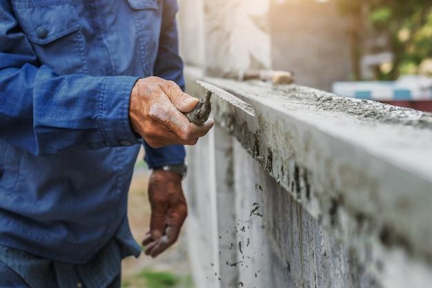 De hand van de close-up van arbeider pleistert