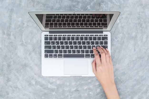De hand van de close-upvrouw het typen op toetsenbord bij de grijze notitieboekjecomputer op concrete bureau geweven achtergrond in de tuin