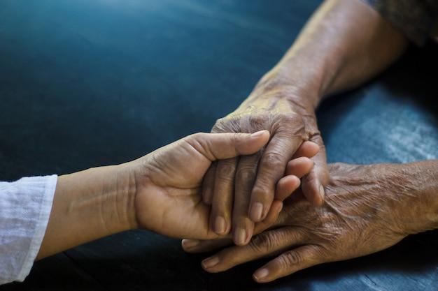 De hand van de dochterholding van moederbejaarden die alzheimer en parkinsonpatiënt is