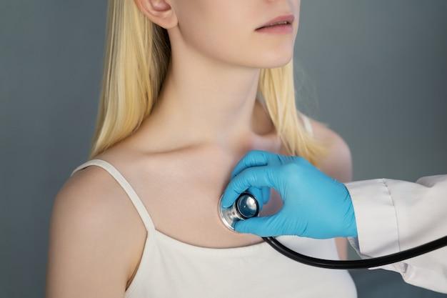 De hand van de dokter in een beschermende handschoen past een stethoscoop toe om naar de ademhaling van het meisje te luisteren.