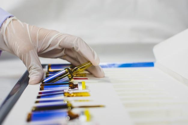 De hand van de dokter pakt de medicijnampulfles uit de doos, het coronavirus-behandelingsconcept, covid-19.