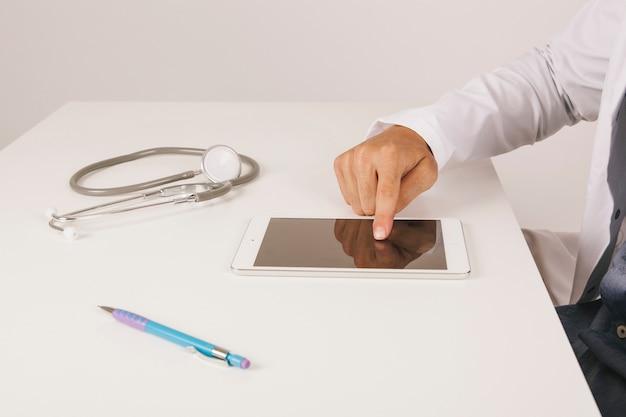De hand van de dokter raakt het scherm van de tablet aan