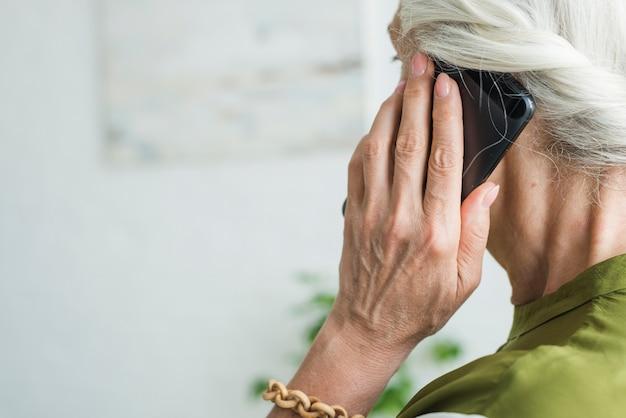 De hand van de hogere vrouw gebruikend cellphone