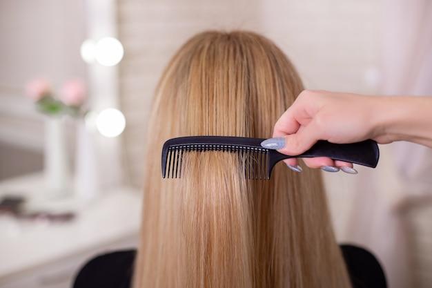 De hand van de kapper die lang natuurlijk blond haar borstelt