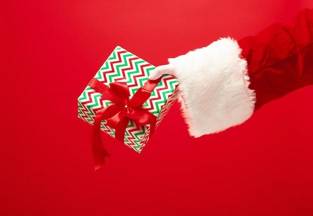 De hand van de kerstman die een geschenk op rood houdt