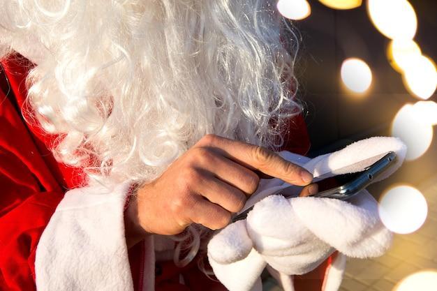 De hand van de kerstman zonder want beweegt zijn vinger over het smartphonescherm. lange witte baard, rood pak. moderne russische grootvader frost. verwerking van de bestelling voor het nieuwe jaar