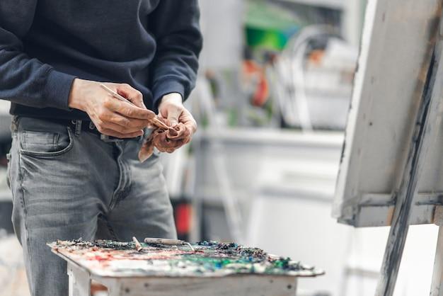 De hand van de kunstenaar houdt een doek en een penseel in handen met een canvas en een palet