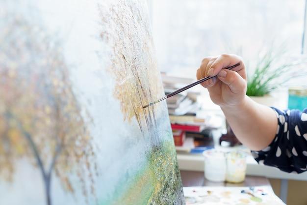 De hand van de kunstenaar trekt olieverfschilderij dicht omhoog