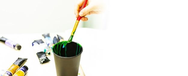 De hand van de kunstenaar wast een penseel met verf in een glas water, een kunstenaarsgereedschap, creativiteit, tekenen, tekentraining, kunstacademie, spandoek.