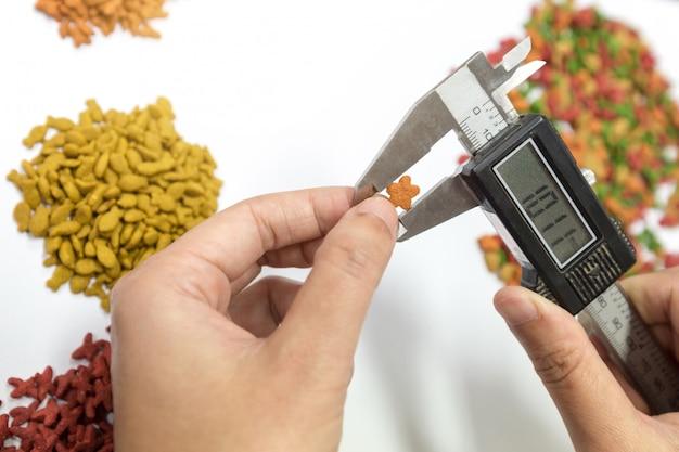 De hand van de kwaliteitscontrole maakt gebruik van verniermaat gemeten brokkelgrootte om de kwaliteit te regelen.