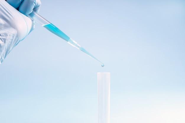 De hand van de laboratoriumassistent houdt een pipet met een oplossing vast en druppelt in een reageerbuis
