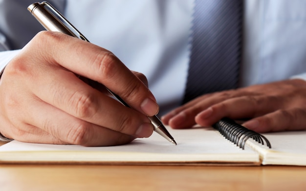 De hand van de man die het conceptboek schreef en het contract ondertekende