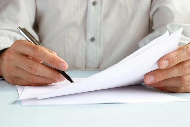 De hand van de man doet aantekeningen in officiële papieren