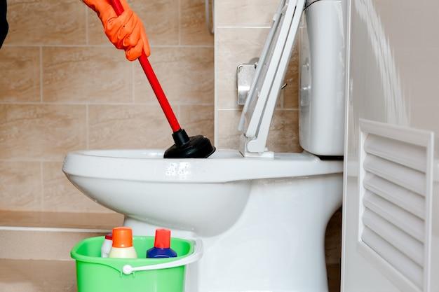 De hand van de man draagt een rubberen handschoen die de spoeling in het toilet schoonmaakt.