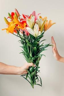 De hand van de man geeft boeket bloemen van lelies aan het meisje en krijgt een weigering