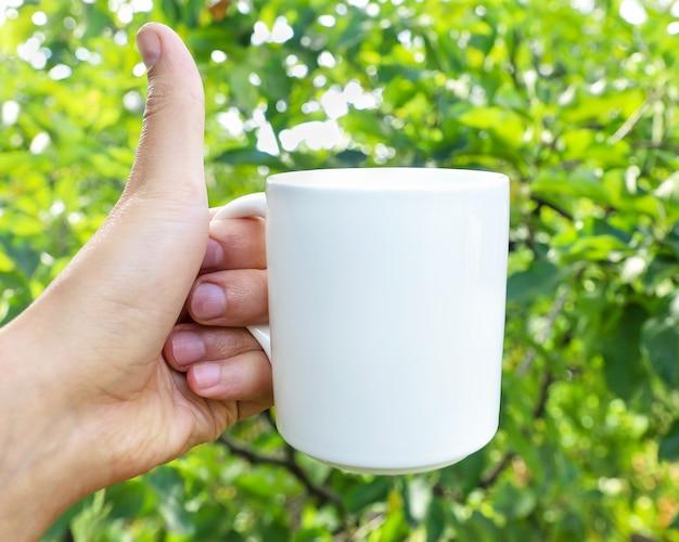 De hand van de man houdt een mock-up beker vast en toont een close-up van de klas op de achtergrond van de natuur