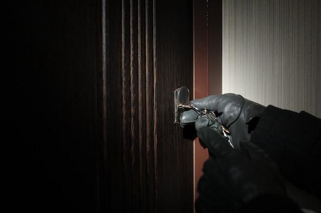 De hand van de man in een sleutel van een handschoen opent de deur