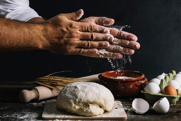 De hand van de mannelijke bakker bestrooit bloem op kneeddeeg