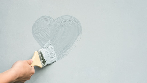 De hand van de meester met een penseel schildert een hart op de muur.