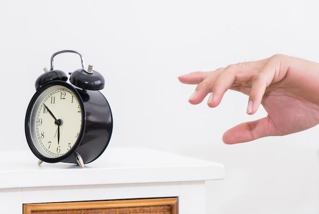 De hand van de mens bereikt wekker in de vroege ochtend