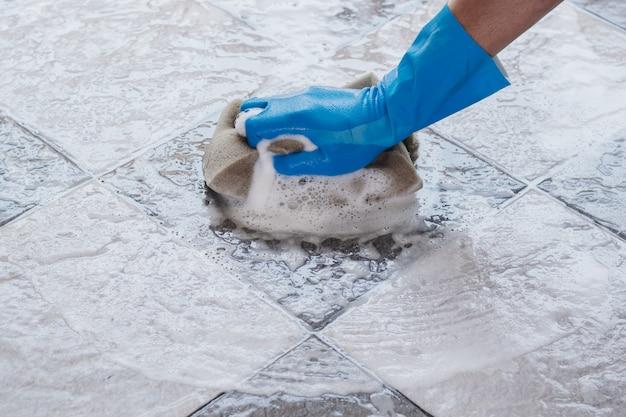 De hand van de mens die blauwe rubberhandschoenen draagt gebruikt een spons schoonmakend de tegelvloer.