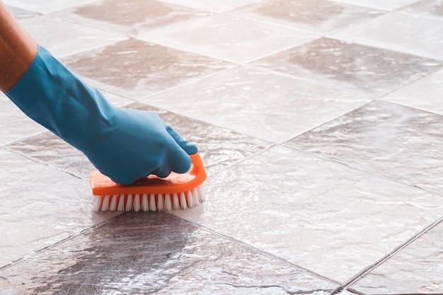 De hand van de mens die blauwe rubberhandschoenen draagt wordt gebruikt om schrobben op de tegelvloer om te zetten.