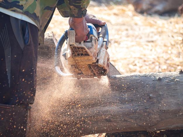 De hand van de mens houdt een handbediende benzinekettingzaag vast die hout snijdt