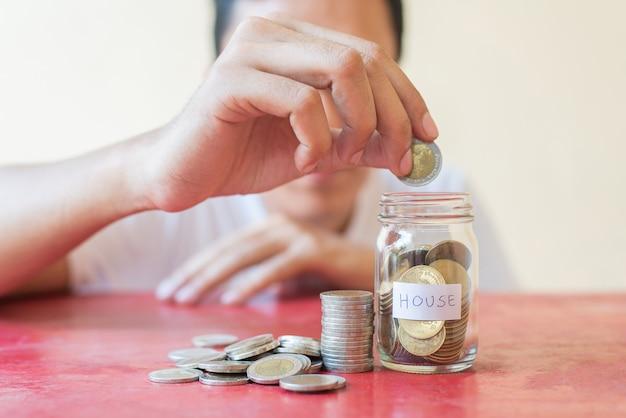 De hand van de mens houdt munt en zet spaarmunten in glas met een stapel munten op rode houten tafel - investeringen, zaken, financiën en bankieren concept