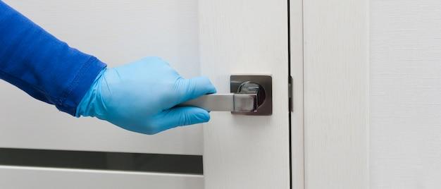 De hand van de mens in een blauwe beschermende handschoenen opent of sluit de deur. antibacteriële profylaxebanner in tijden van virussen