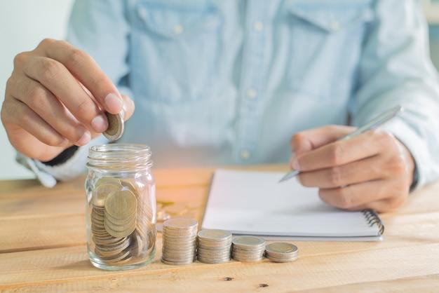 De hand van de mens munt in het glas en schrijven op laptop op houten werktafel met stapel munten - investeringen, zaken, financiën en bankwezen