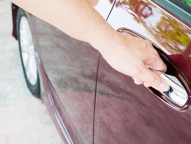 De hand van de mens opent autodeur